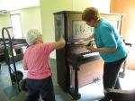 Dee Adams and Lynn Dinwoodie polish the piano for Sunday's service